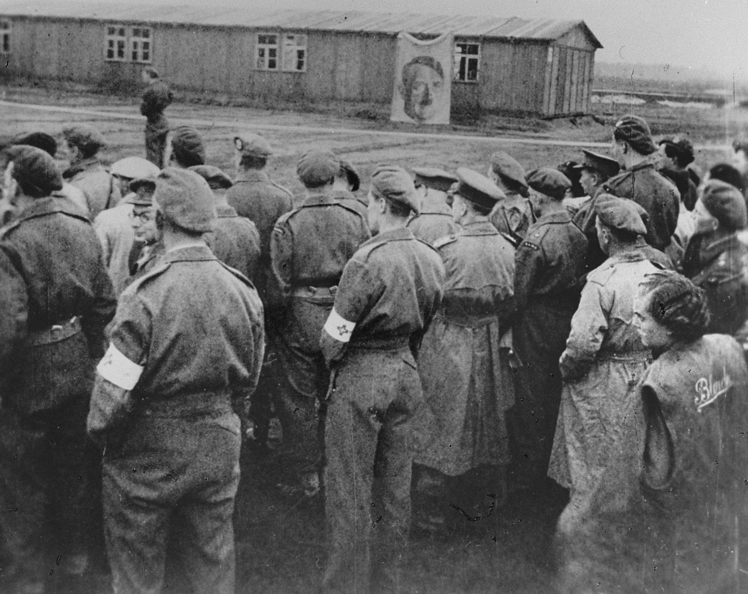 British troops look on as the last Typhus ridden barracks in Belsen are burned.