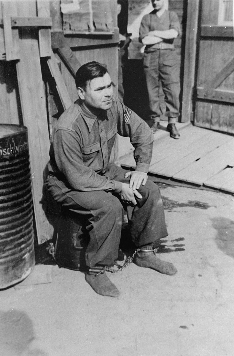 Shackled and under guard, Josef Kramer, formerly the commandant of Auschwitz-Birkenau killing center and Bergen-Belsen concentration camp, awaits his fate.  He was later hanged for his crimes.