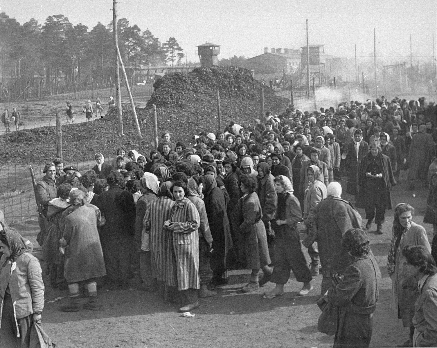 Women survivors of Bergen-Belsen crowd together on the main street of the camp to wait for food.  A pile of victims' shoes is visible in the background.