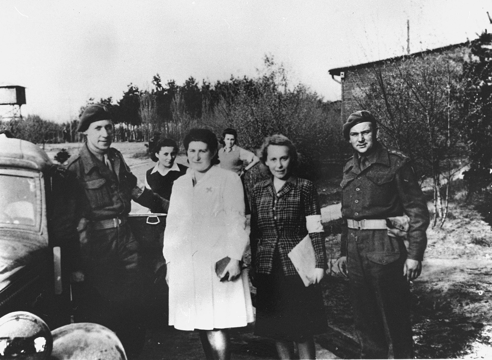 Survivors pose with British soldiers soon after the liberation of Bergen-Belsen.  Among those pictured is Hadassah Bimko (second from the left), Captain Winterbottom, and Dr. Ruth Gutman.