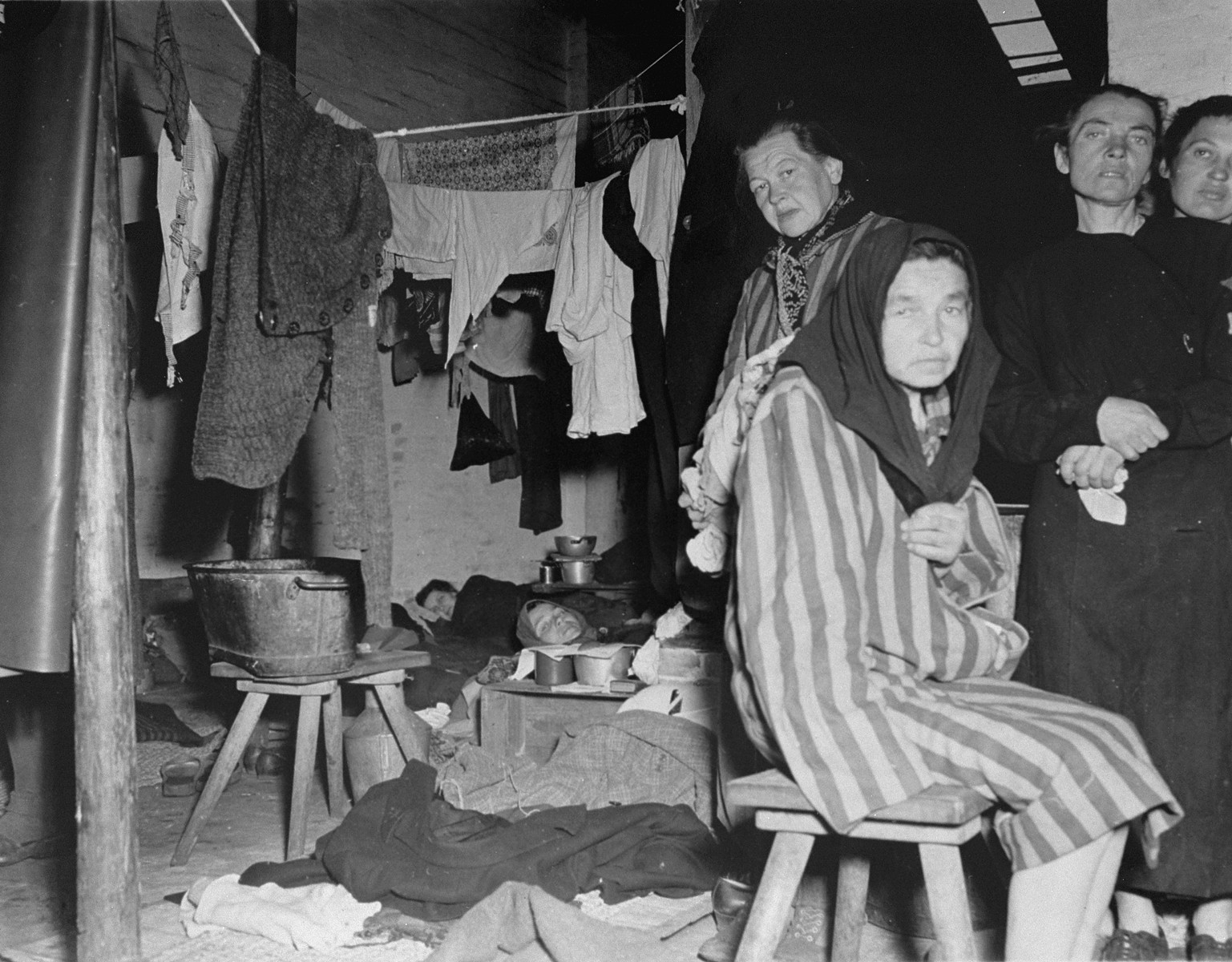"Female survivors inside a  barracks in Bergen-Belsen after liberation.  The original caption reads: ""Interior of women's barracks in former Nazi prison camp at Belsen, Germany, showing pitiful conditions under which they were forced to live."""