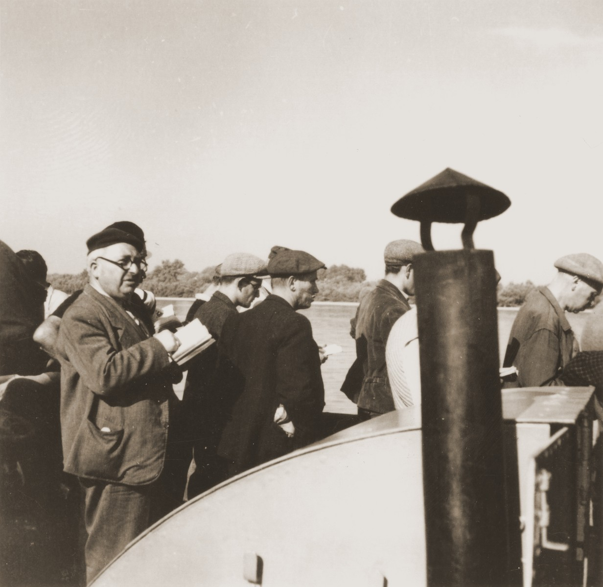 Jewish refugees from the Kladovo transport participate in a morning prayer service on the deck of a riverboat travelling from Kladovo to Sabac.