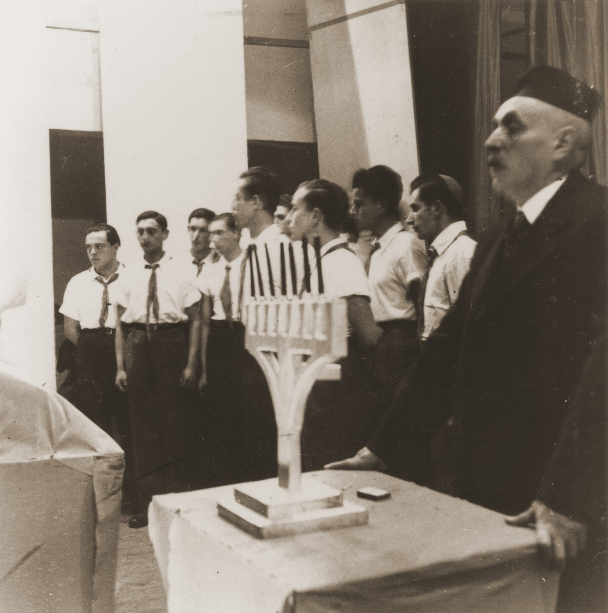 Members of the Kladovo transport lead a Hanukkah candlelighting ceremony at the Sabac refugee camp.
