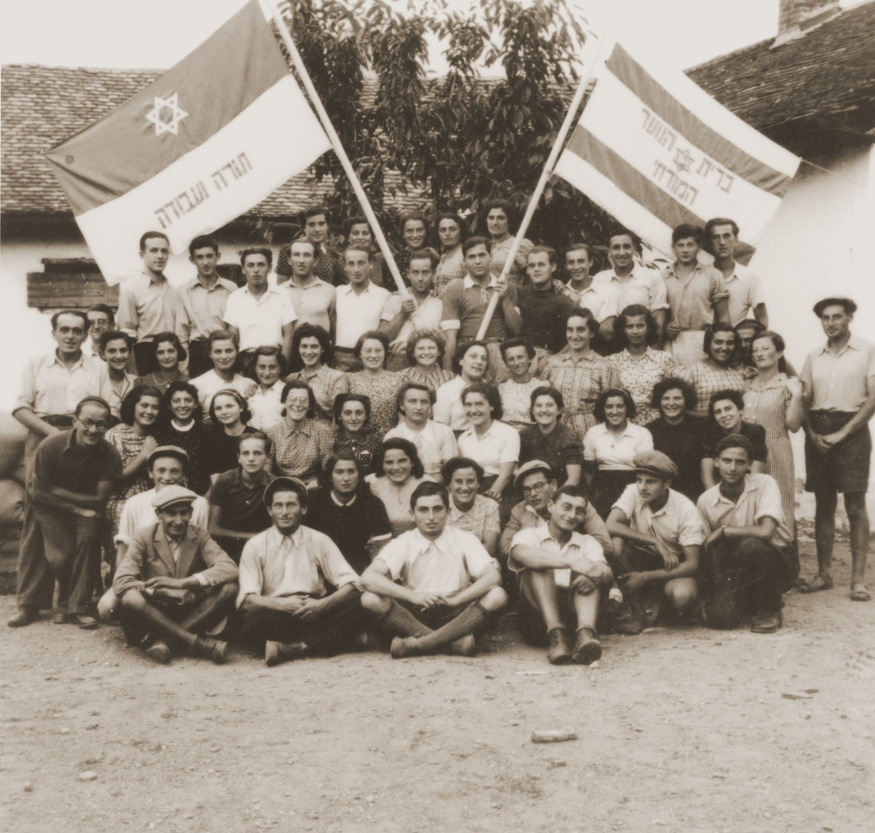 Members of the Brit Hanoar Hamizrahi from the Kladovo transport pose with the Zionist flag.