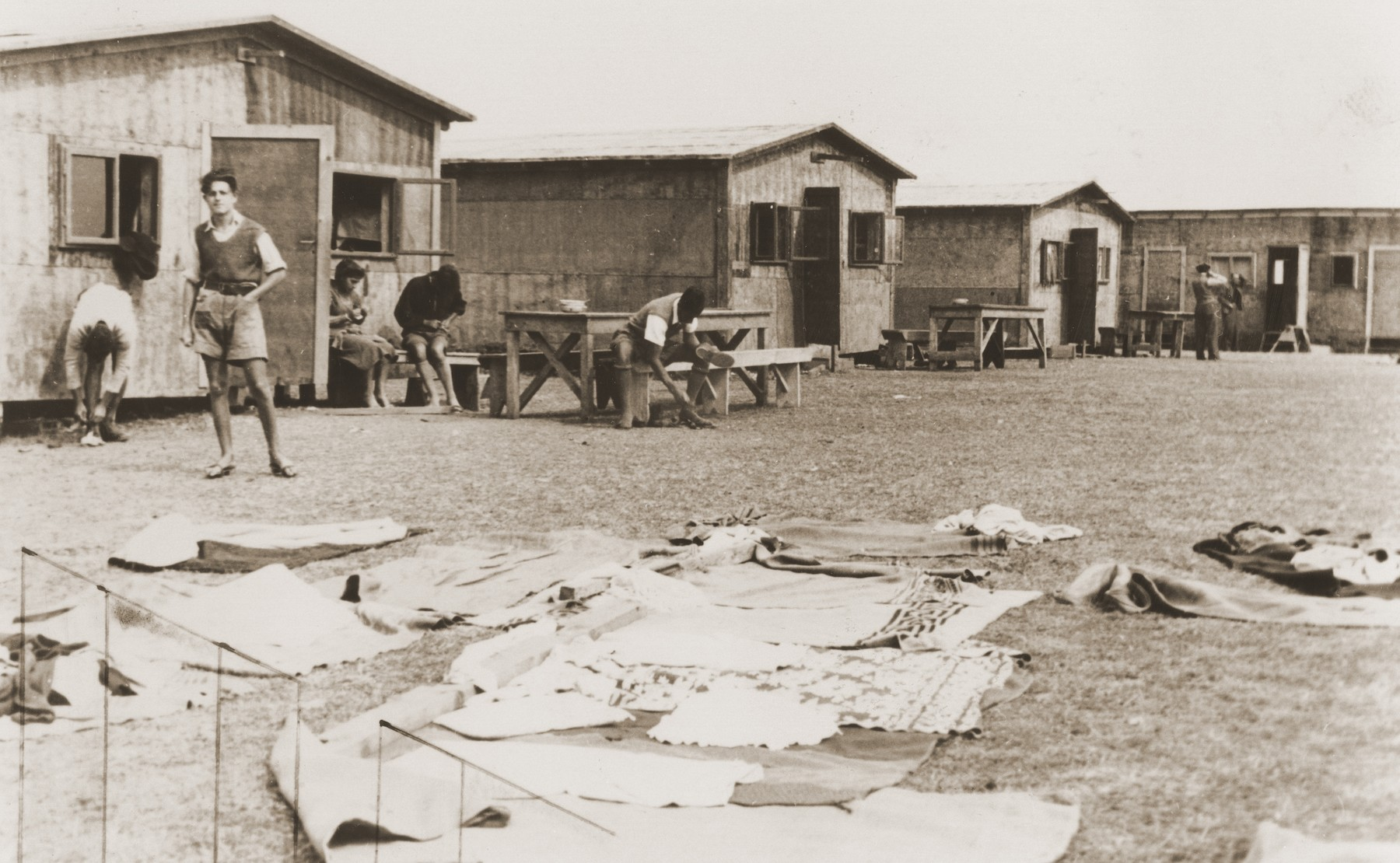 At a refugee camp established for members of the Kladovo transport, Zionist youth perform their daily tasks in front of their barracks.