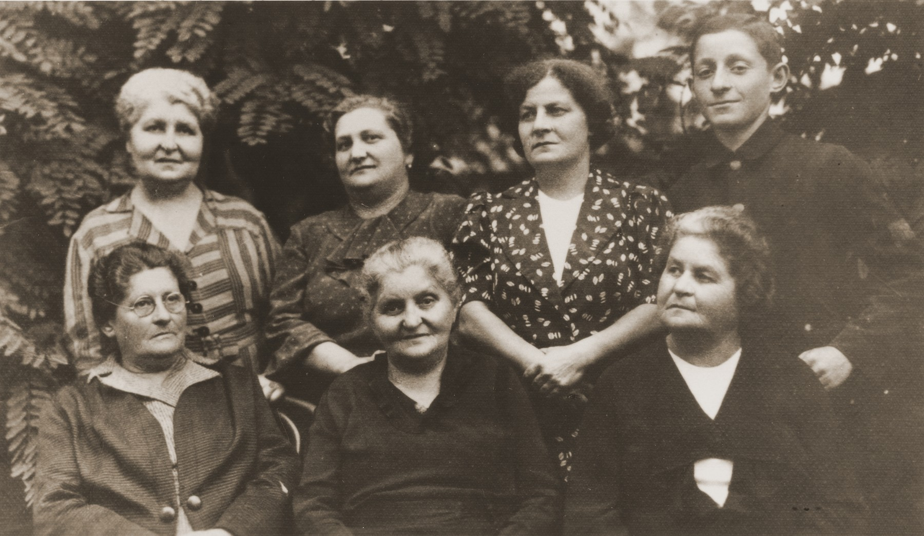 Emma Wurmbrand Hirsch with her four sisters, niece and nephew.    Pictured standing from left to right are:  Berta Wurmbrand Vogel; Sidi Silberbusch Star; Shulamith Wurmbrand; and Yochanan Wurmbrand.  Seated from left to right are:  Emma Wurmbrand Hirsch; Pepi Wurmbrand Silberbusch; Lotti Wurmbrand Roth.