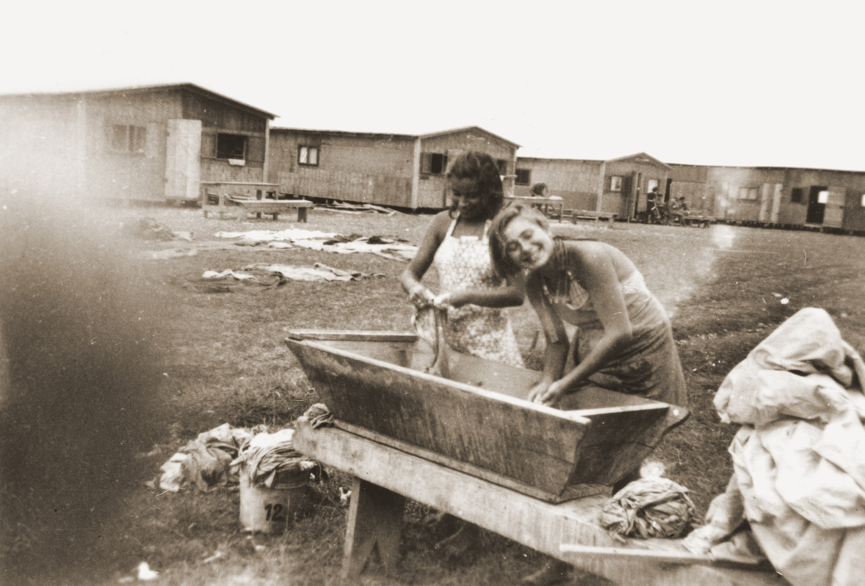 At a refugee camp established for members of the Kladovo transport, two Jewish girls do the laundry in a trough outside their barracks.