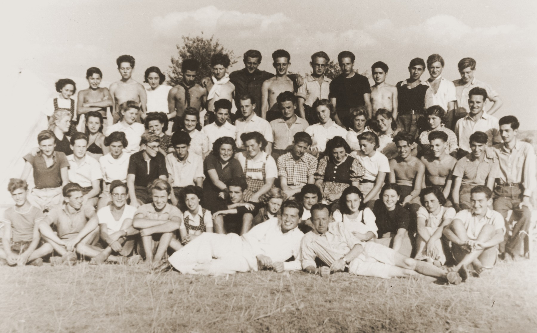 Group portrait of Zionist youth from the Kladovo transport.  The majority of those pictured immigrated to Palestine in March 1941.    Erich Nachaeuser is pictured standing in the top row, fifth from the left.  Ruth Weisz is second row, sixth from the right and Seppl Baumgartner is to her left.