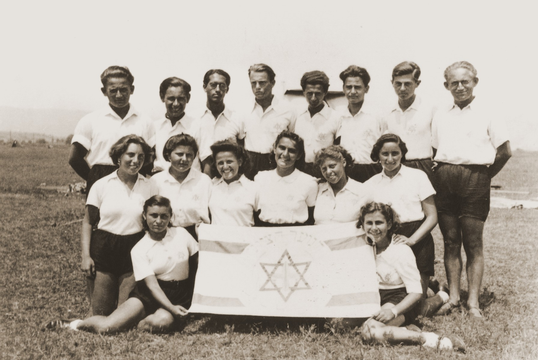 Members of the Zionist youth group Hanoar Hatzioni pose with their movement's flag at a refugee camp for the Kladovo transport.  Standing third from the right is Egon Ostreicher.  Second from the right is Nachum Tabak.
