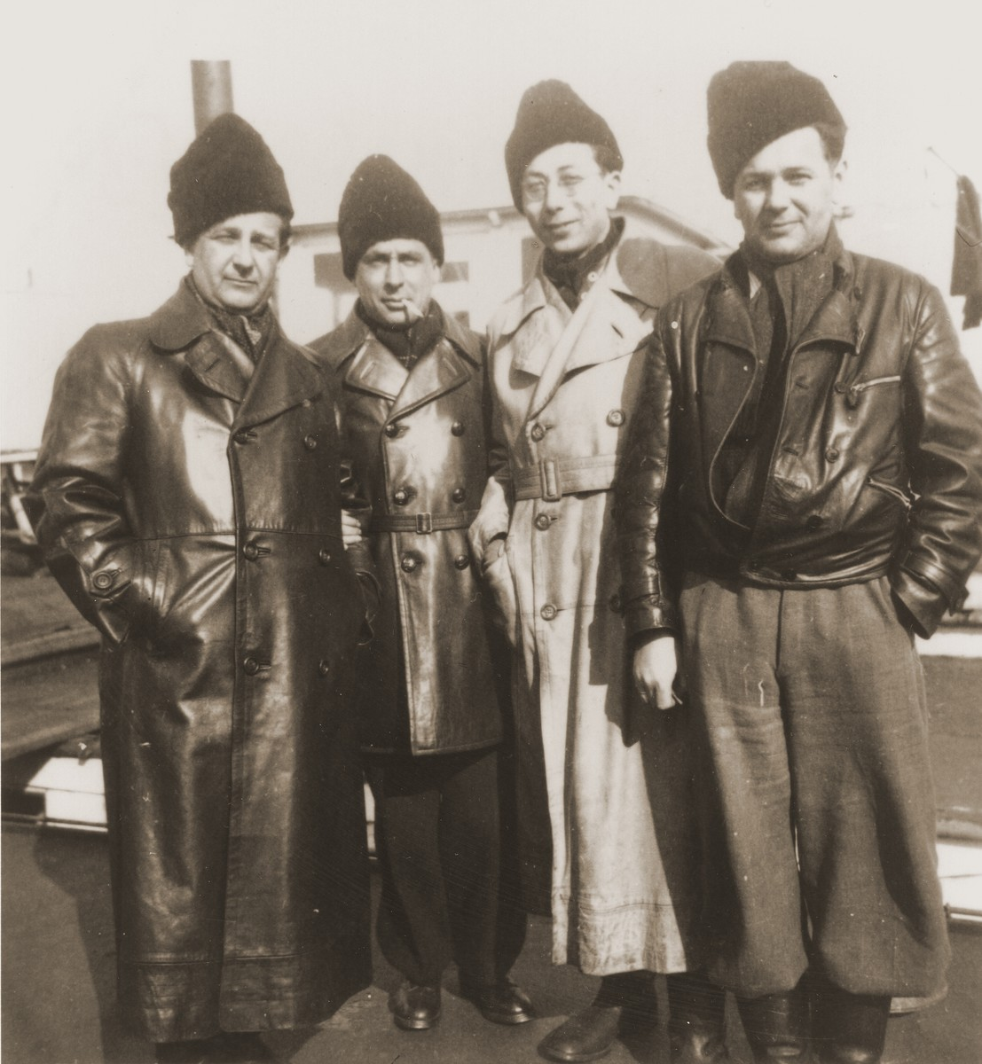The leaders of the Kladovo transport stand on the deck of a riverboat docked in Kladovo harbor.  Pictured from right to left are Jozsi Schaechter, Jukl Dorfmann, Bata Gedalja and Emil Schaechter.
