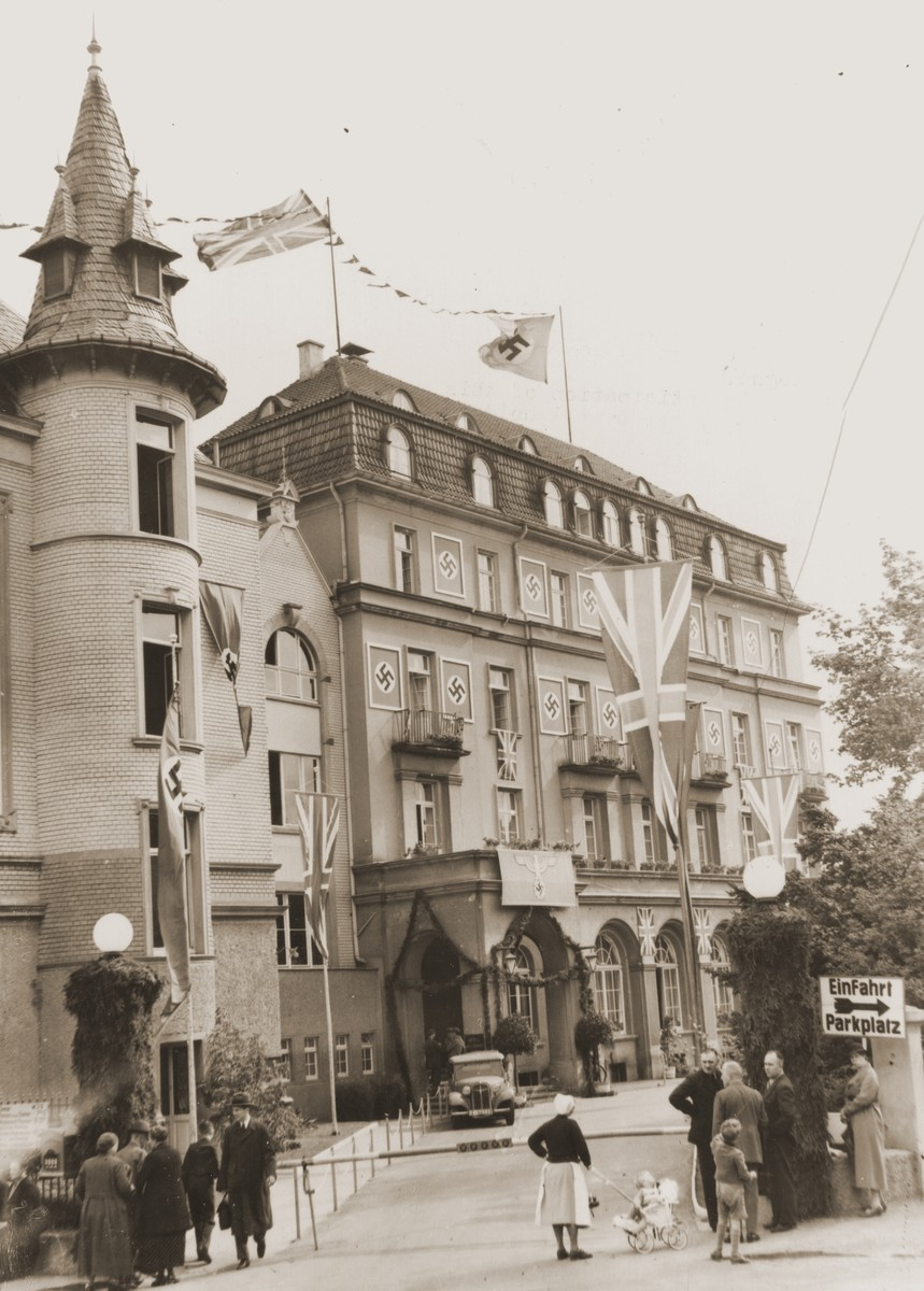 German citizens stand outside the decorated Hotel Dreesen where Adolf Hitler and British Prime Minister Neville Chamberlain are to hold their second meeting to decide the fate of Czechoslovakia.