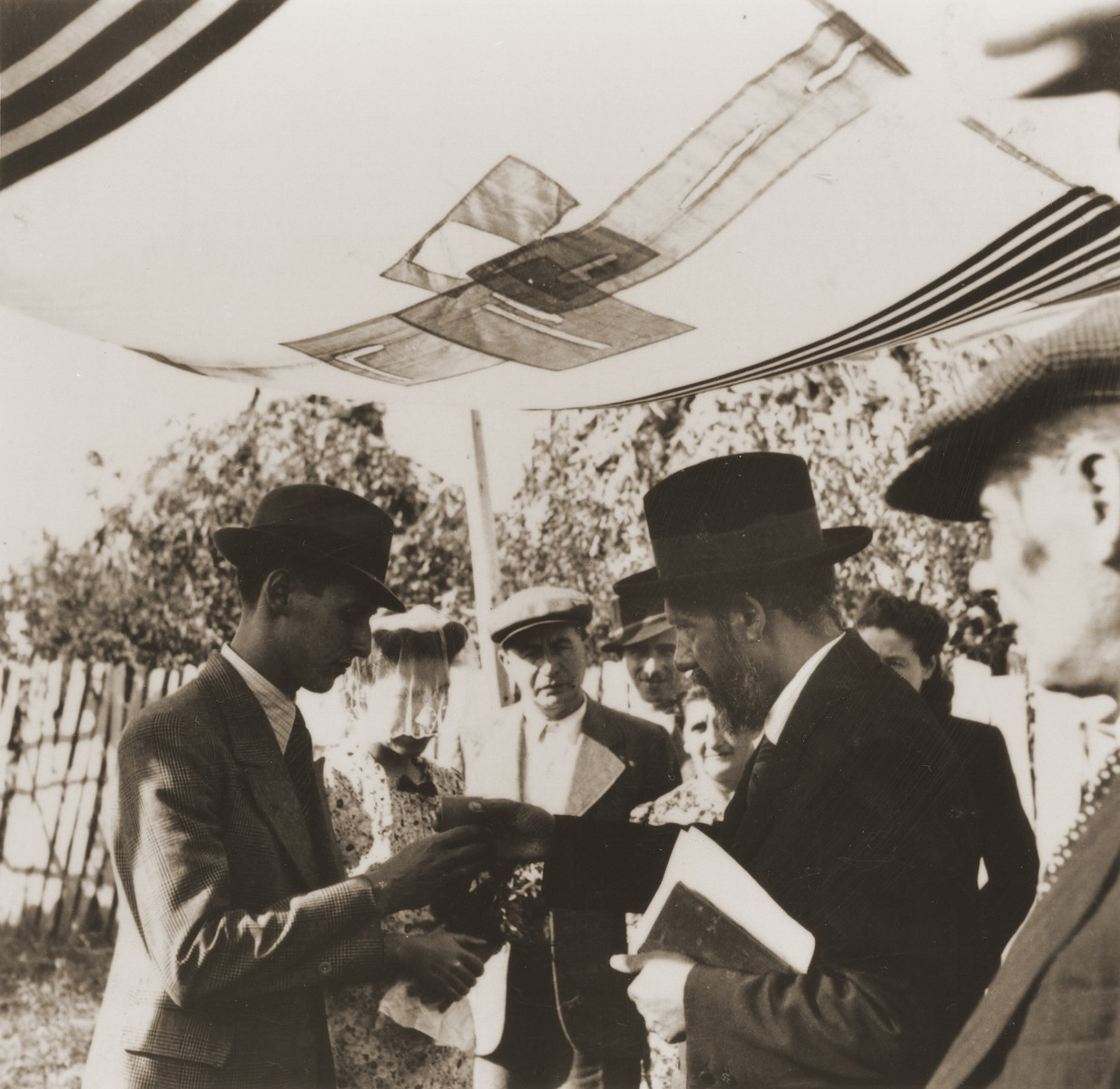 A Jewish refugee couple from the Kladovo transport are married outside under a chupa [canopy].
