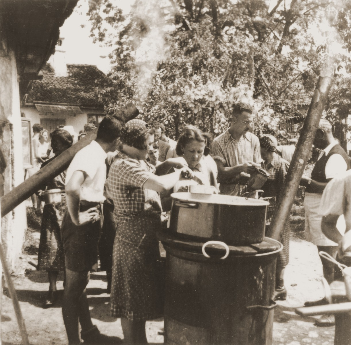 Jewish refugees from the Kladovo transport queue up to receive a meal at a refugee camp.