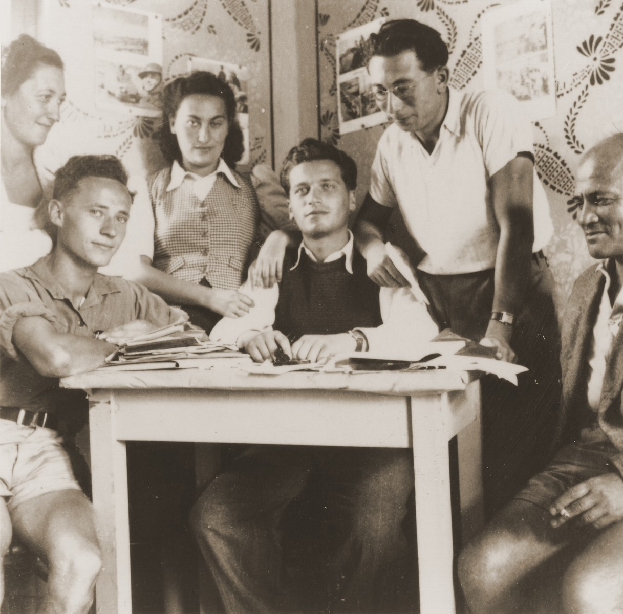 Zionist  youth from the Kladovo transport gather around a table at the movement's headquarters.  Among those pictured are: Klara Shula-Dorfmann (middle) and Jukl Adolf Dorfmann.