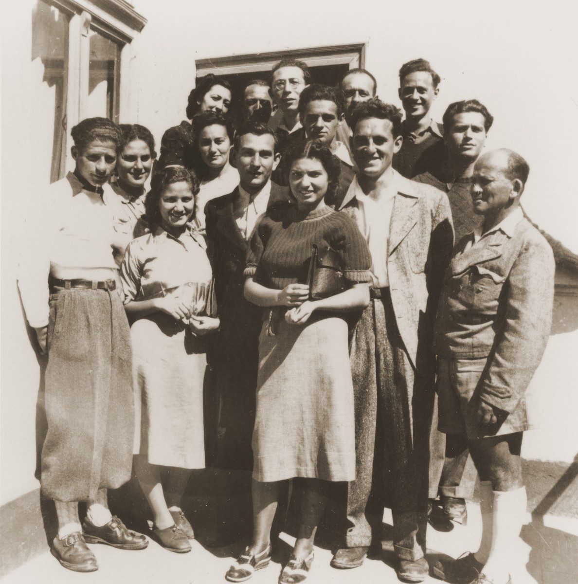 Group portrait of Zionist youth from the Kladovo transport taken after the triple wedding of members of their group.    Among those pictured are: Erich Nachhaeuser (far left), Jukl Dorfmann (top row, middle, wearing glasses), and Klara-Shula Dorfmann (middle row, second from left).