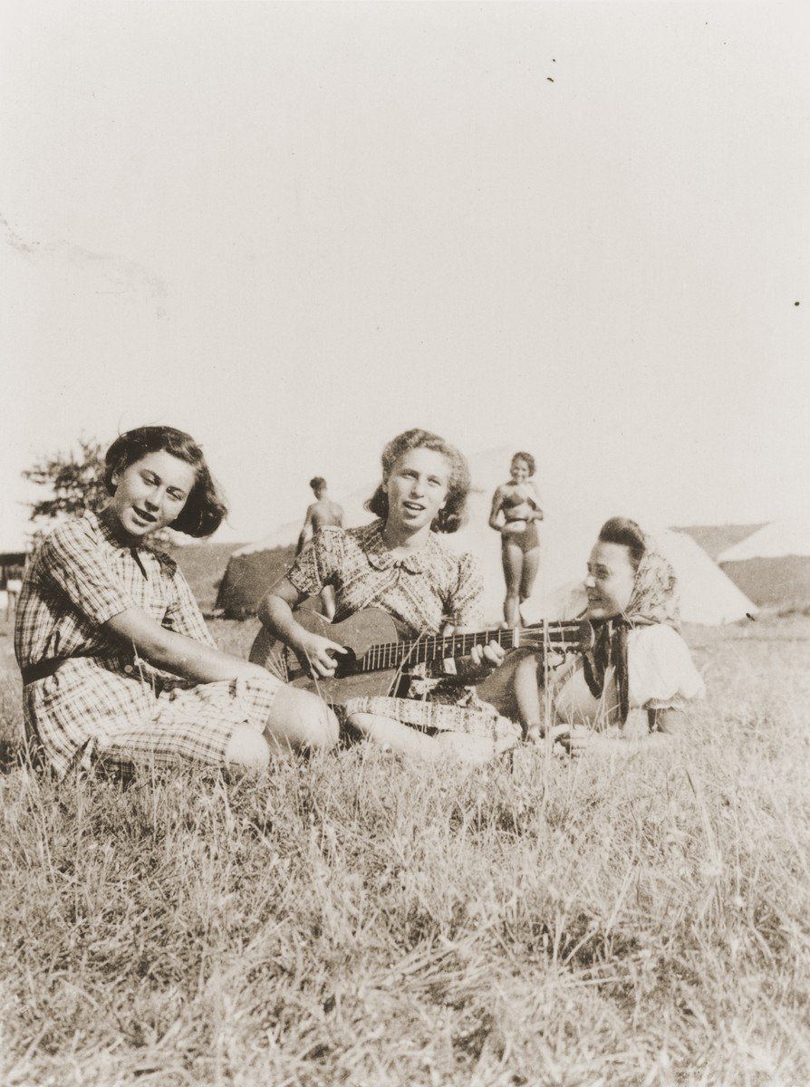Three teenage girls sing with guitar accompaniment at the Zionist youth camp in Kladovo.  Among those pictured are Trude Westwood (left) and Hani Berger (right), both of whom survived the war.