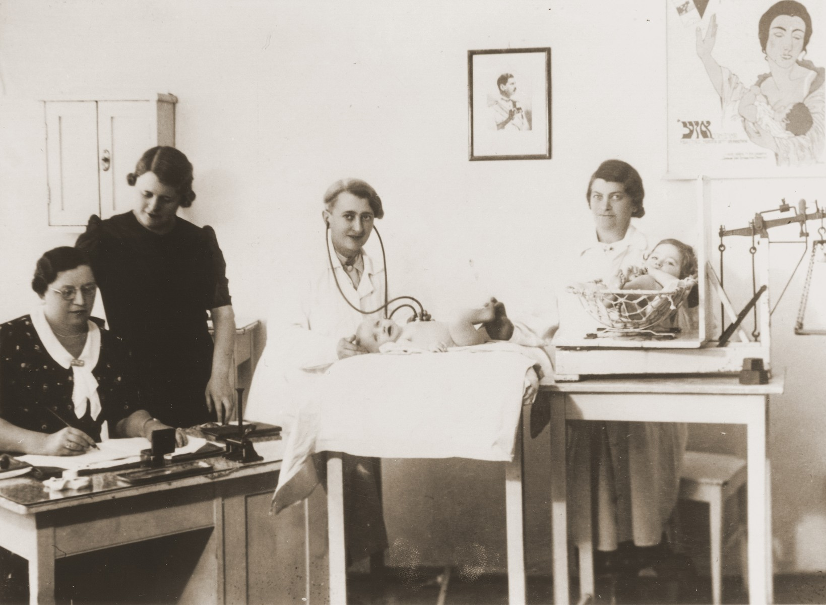 Infants are weighed and examined at the OSE clinic in Cernauti, Romania.   Among those pictured are Anny (Hubner) Andermann (second from the left), president of the OSE; Dr. Salter, (center), OSE pediatrician; and Mrs. Zappler (right), an assistant.  Behind them on the wall is a portrait of King Carol of Romania.