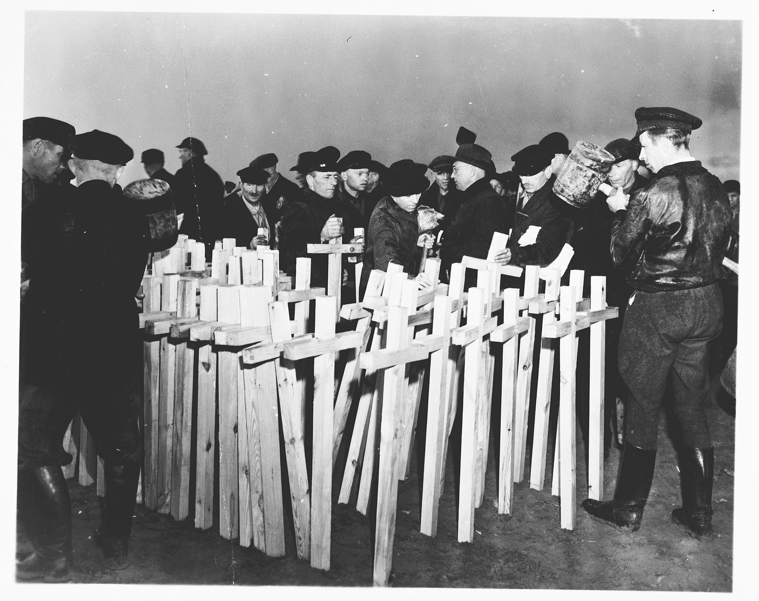 German civilians place wooden crosses beside the gravesite where concentration camp prisoners, who were killed by the SS in a barn just outside Gardelegen, will be interred.