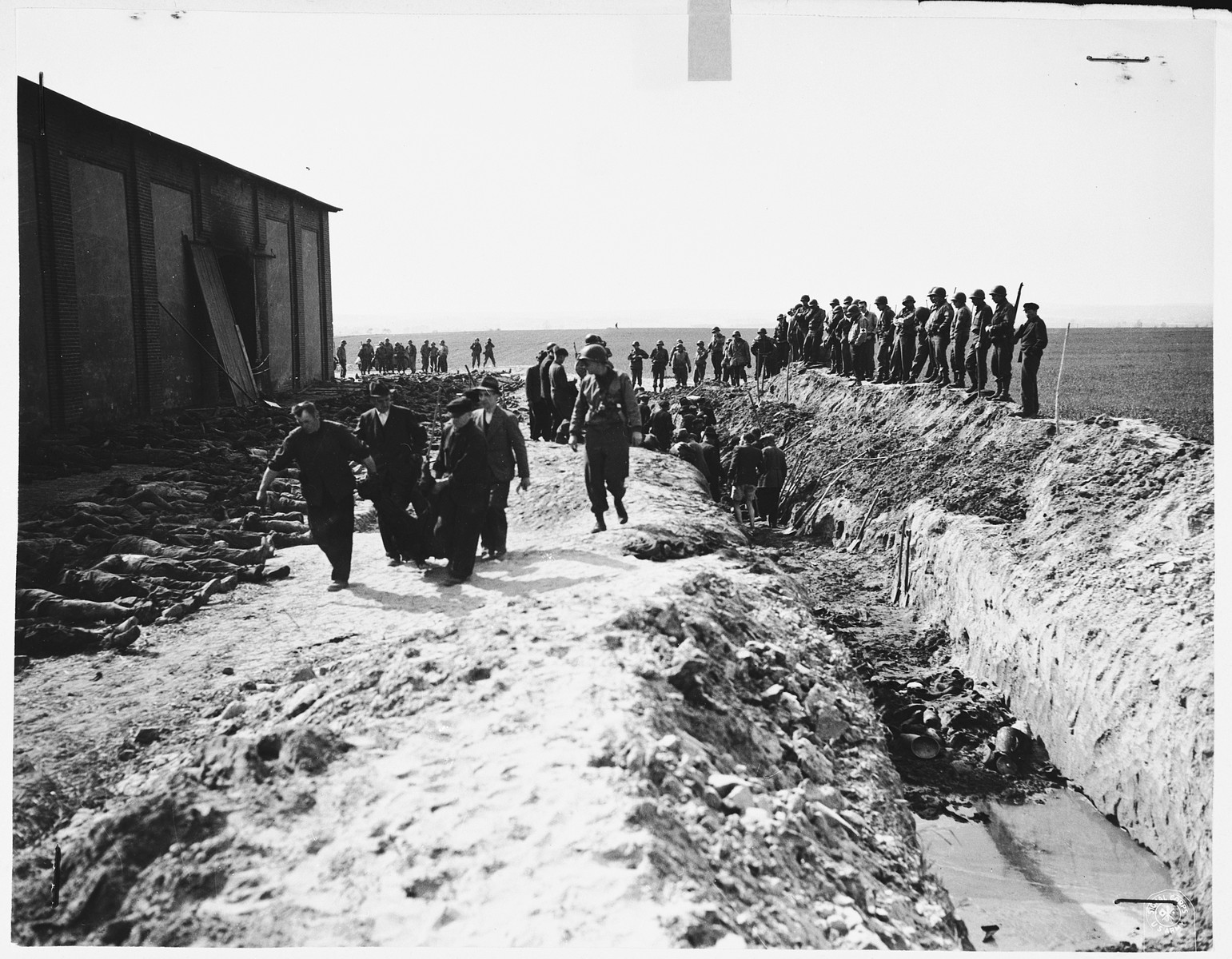 Under the supervision of American soldiers, German civilians remove corpses from a mass grave on the north side of the barn outside of Gardelegen.