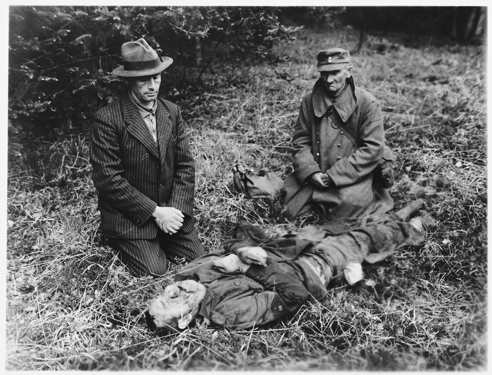 A Nazi party member from Hals and a German prison guard kneel beside the body of a Russian slave laborer who was killed by SS troops near Tiefenbach, near Passau.   They were forced to view the atrocity by U.S. Third Army troops.  The victim was one of 100 Russians interned in a barn in Oberjacking, a small village near Tiefenbach.