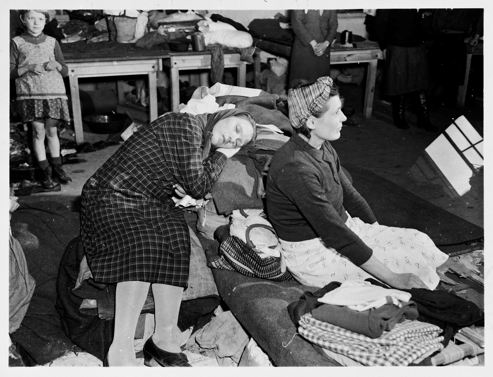 Female survivors rest in the Ernst Leitz Optical works in Wetzlar after their liberation by American troops with the First Army.    These workers from Poland and the Ukraine were captives for the past three years.  They worked from 5am to 6pm daily, and were fed a steady diet of beet soup and black bread.