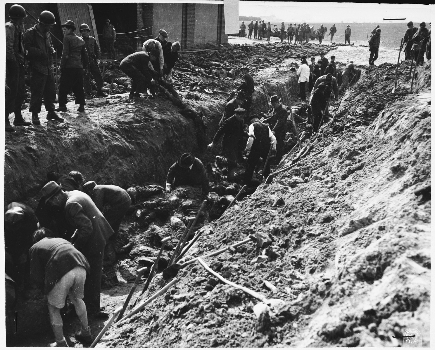 Under the supervision of American soldiers, German civilians exhume a mass grave containing the bodies of prisoners killed by the SS in a barn just outside Gardelegen.