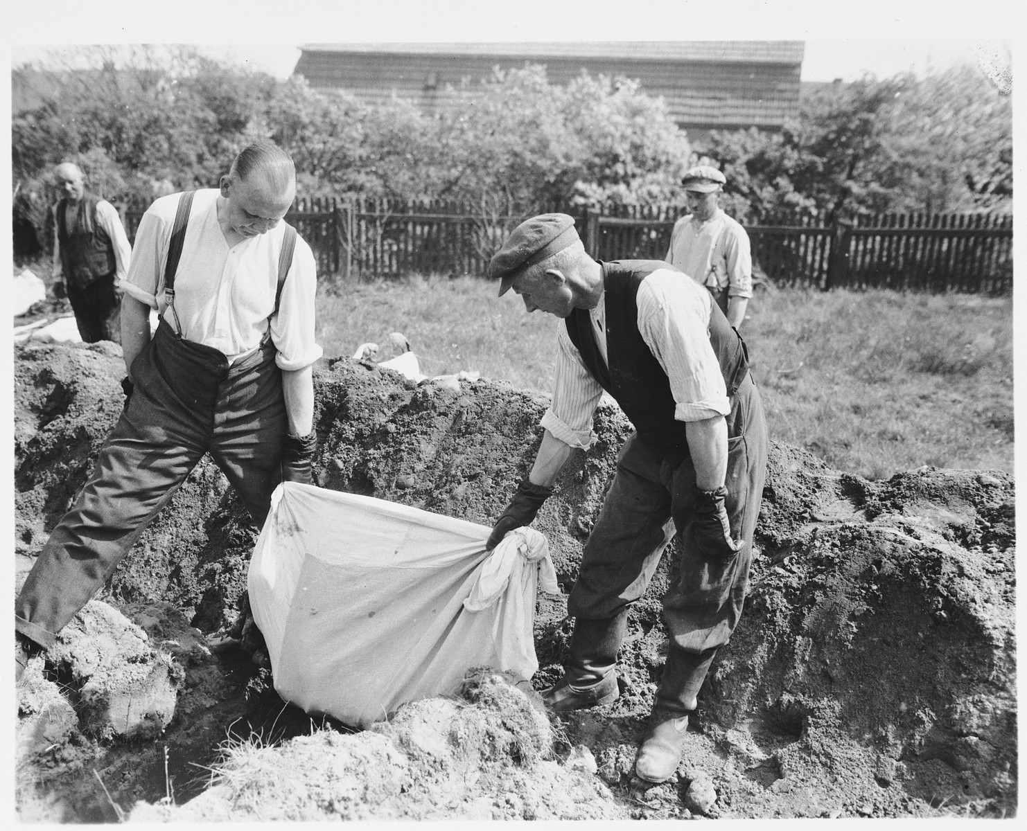 German civilians from Estedt remove the bodies of Polish, Russian and Jewish slave laborers from a mass grave for proper reburial.
