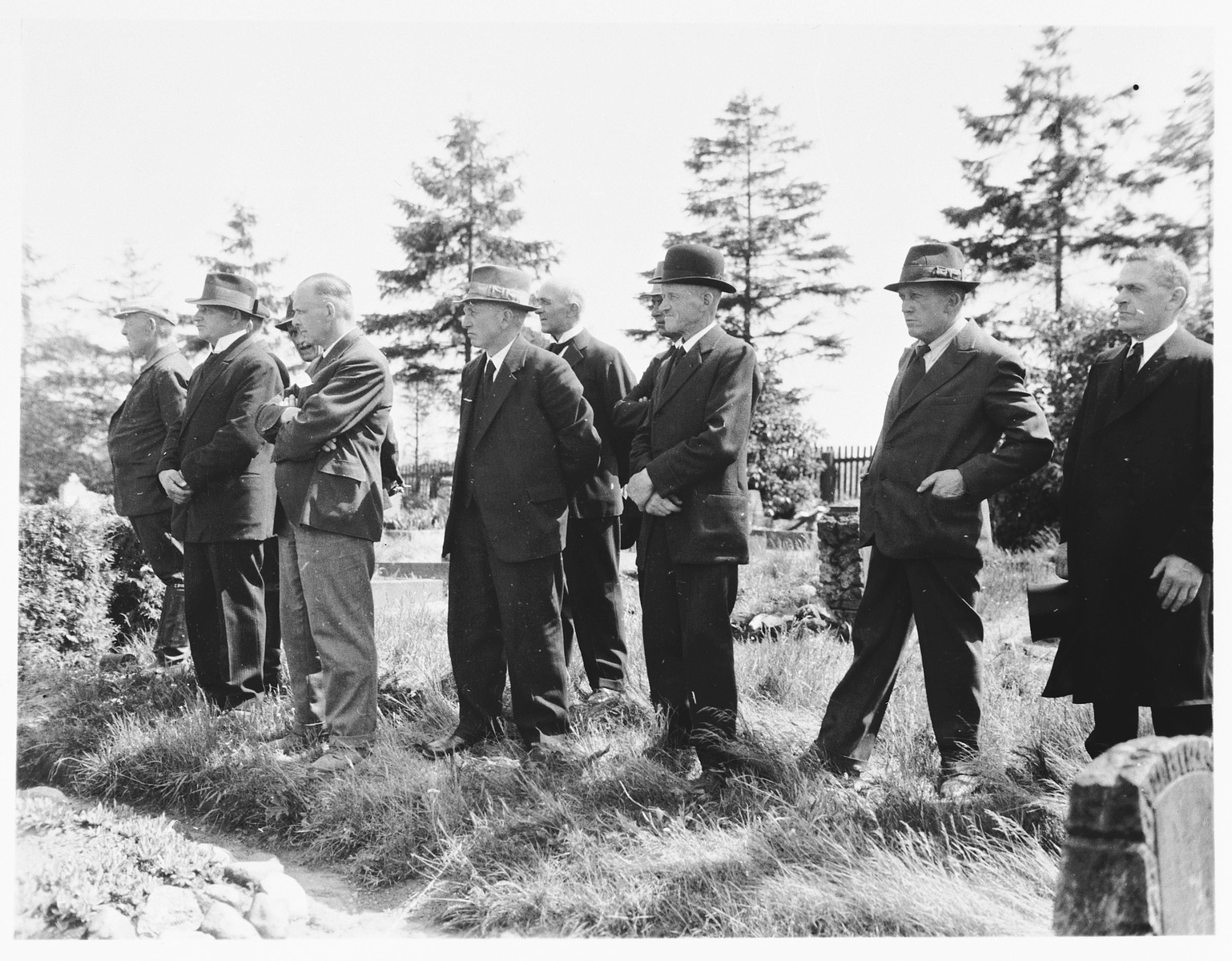 German civilians from Estedt attend the funeral services performed by a Catholic priest for prisoners exhumed from a mass grave near the town.
