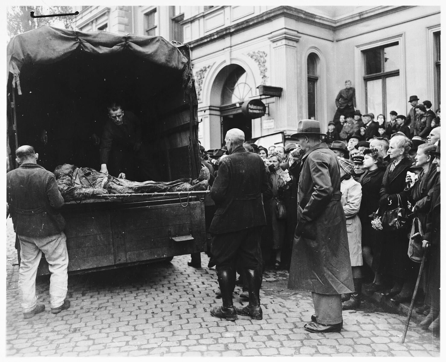 Under the direction of American soldiers, German civilians transport the bodies of 71 political prisoners, exhumed from a mass grave near Solingen-Ohligs, to new graves in front of the city hall.    The victims, most of whom were taken from Luettringhausen prison, were shot and buried by the Gestapo following orders to eliminate all Reich enemies just before the end of the war.