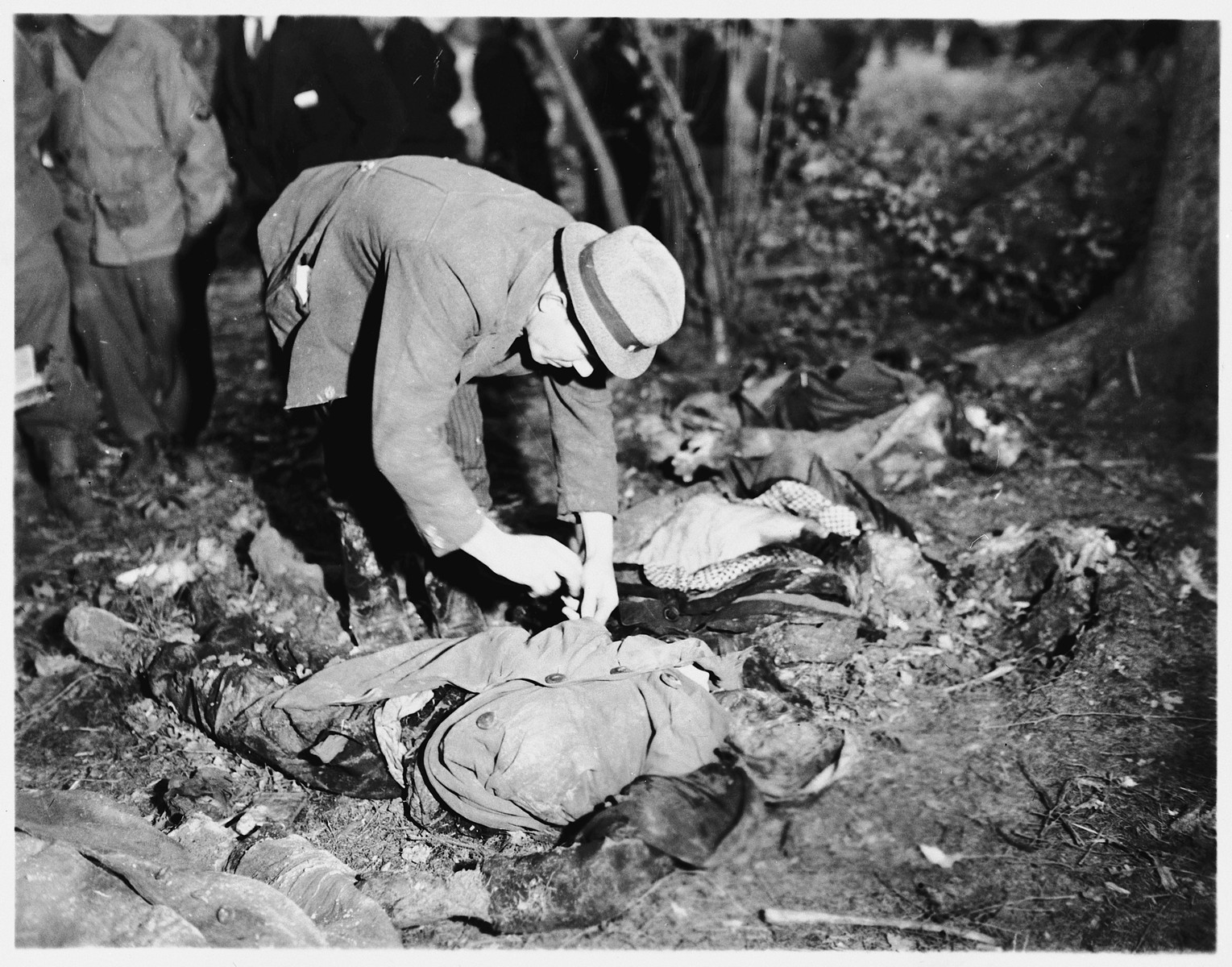 A man looks for identification papers on one of the 57 corpses of Russians, including women and one baby, exhumed from a mass grave near Suttrop.    The victims were forced to dig their own grave and then were shot by SS troops six weeks before the arrival of American troops.  On May 3, 1945, the 95th Infantry Division of the U.S. Ninth Army arrived in Suttrop and were informed by locals of the mass grave.  American troops forced the townspeople to exhume the grave after which Russian displaced persons in the area identified the bodies.  The victims were reburied in individual graves, and a U.S. Army chaplain conducted burial services.  Russians remaining in the area placed wreaths on the graves.