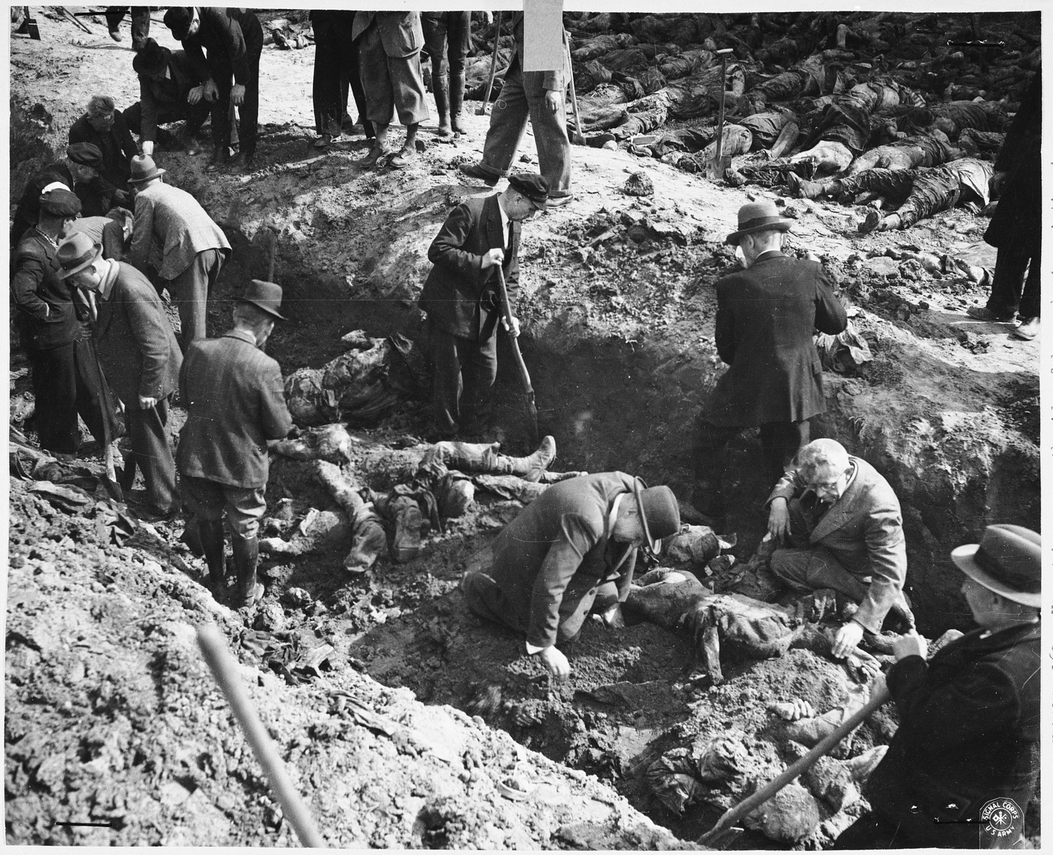 German civilians exhume a mass grave containing the bodies of concentration camp prisoners killed by the SS in a barn just outside Gardelegen.
