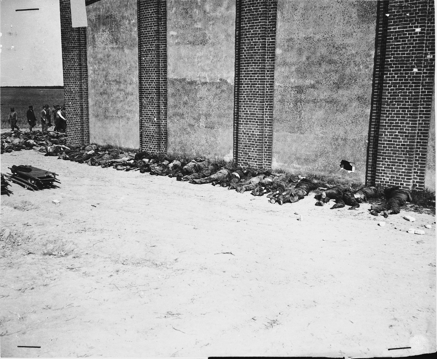 Corpses lined up on the west side of the barn with a visible hole supposedly made by a Panzerfaust.  In the background German civilians remove corpses from the barn.
