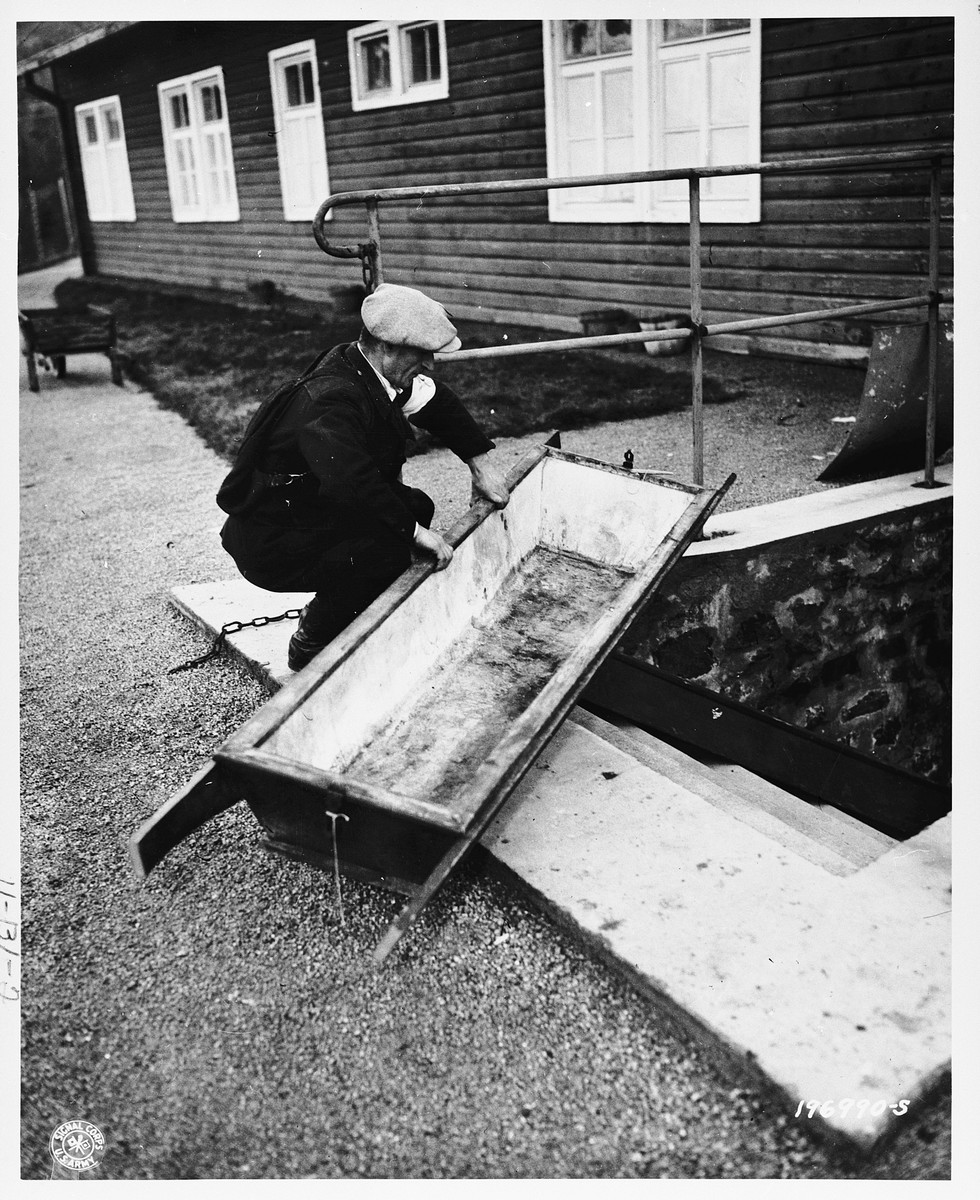 A member of the French resistance examines a blood-stained coffin used by camp personnel to remove bodies from the camp gas chamber.
