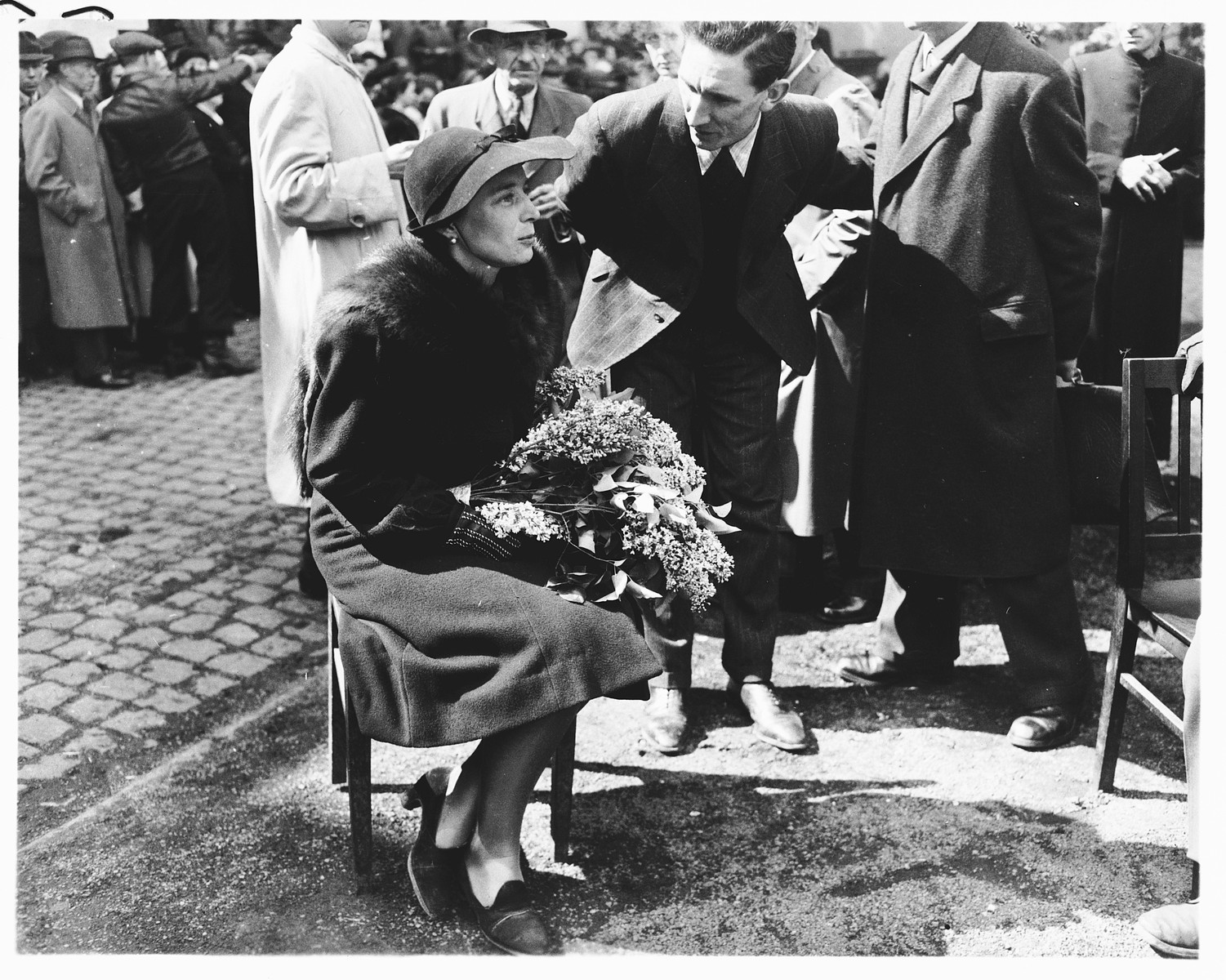 A woman bearing flowers attends the funeral and reburial of 71 political prisoners, exhumed from a mass grave near Solingen-Ohligs, in front of the city hall.    The victims, most of whom were taken from Luettringhausen prison, were shot and buried by the Gestapo following orders to eliminate all Reich enemies just before the end of the war.