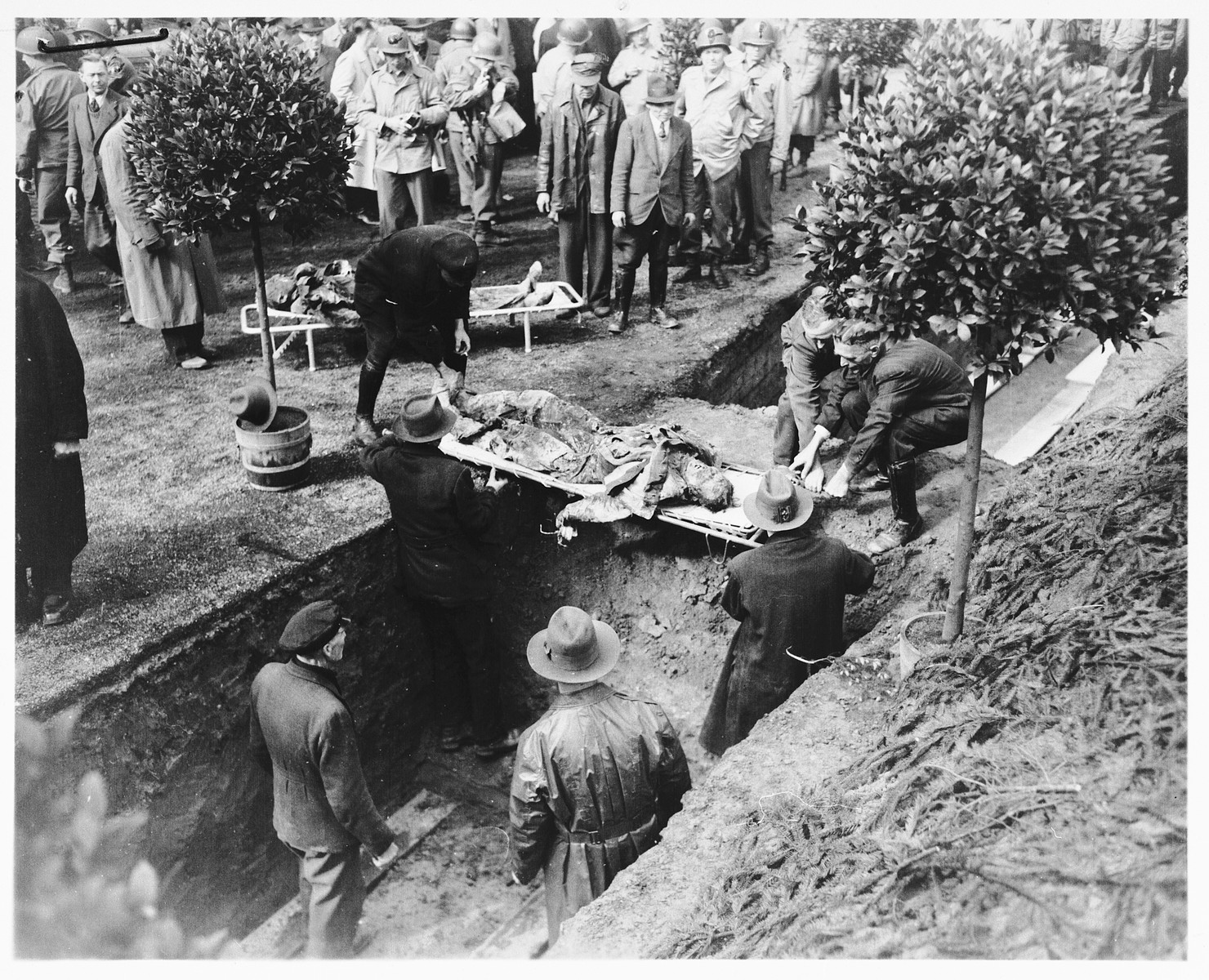 Under the direction of American soldiers, German civilians rebury the bodies of 71 political prisoners, exhumed from a mass grave near Solingen-Ohligs, in front of the city hall.    The victims, most of whom were taken from Luettringhausen prison, were shot and buried by the Gestapo following orders to eliminate all Reich enemies just before the end of the war.