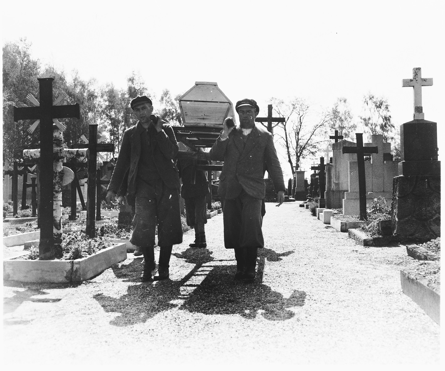 German civilians carry a coffin containing the corpse of a prisoner exhumed from a mass grave near Schwarzenfeld through the town cemetery.    The victim was one of 140 Hungarian, Russian, and Polish Jews killed while on an evacuation transport from the Flossenbuerg concentration camp.