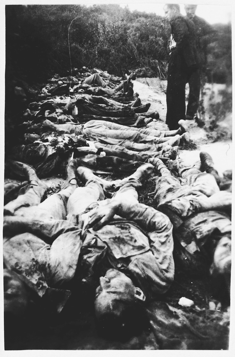 Two civilians stand among the bodies of 44 French hostages who were killed by German soldiers in Premilhat, near Montlucon, on August 14, 1944.