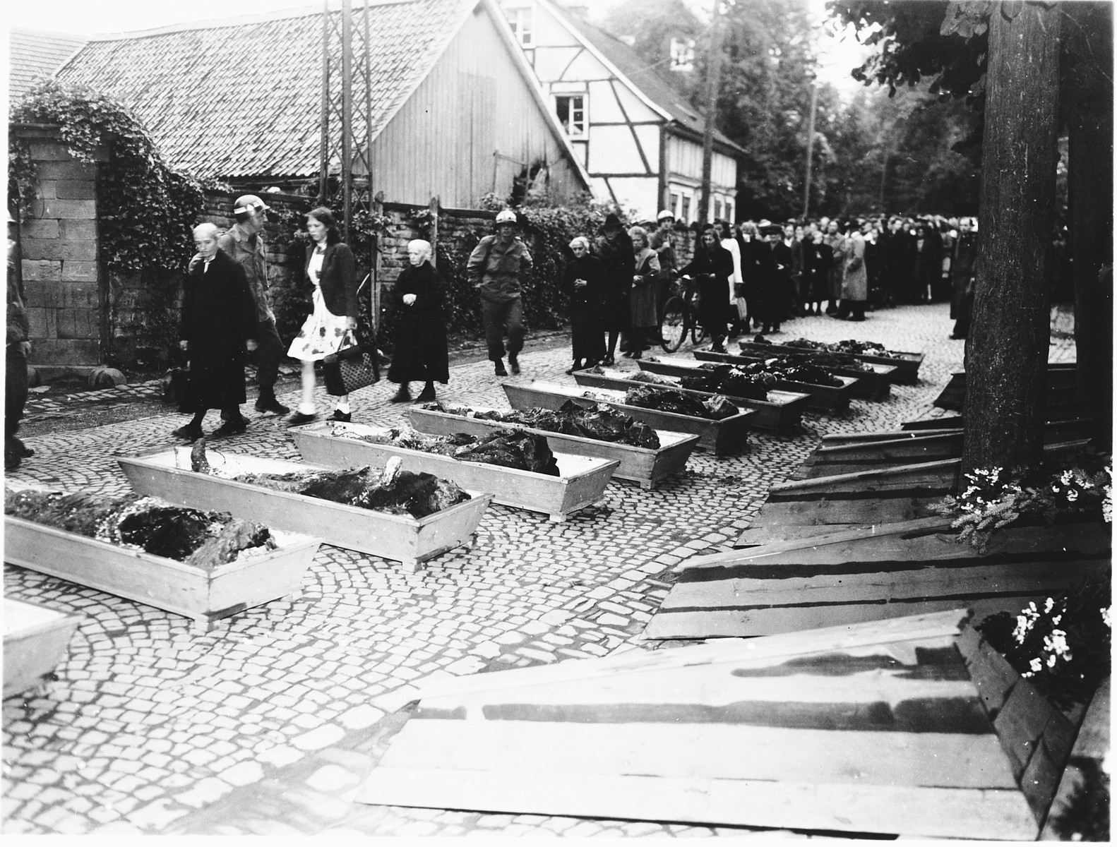 German civilians from Lindlar are forced to look at the exhumed bodies of ten Russians, which had been thrown into a ravine and buried.   The victims were shot on April 4, 1945, by members of the Volkssturm (civilian militia) in retaliation for the killing of the local group leader (SS, SA?) in Overath.