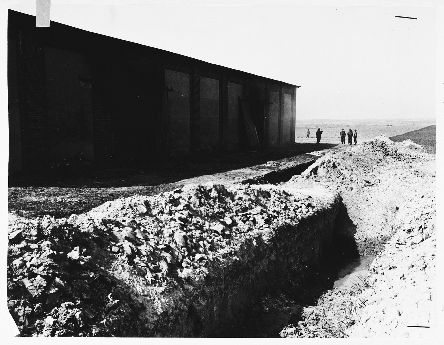View of the north side of the barn outside of Gardelegen.  In the foreground are two mass graves in which prisoners who were burned alive were buried by the SS.