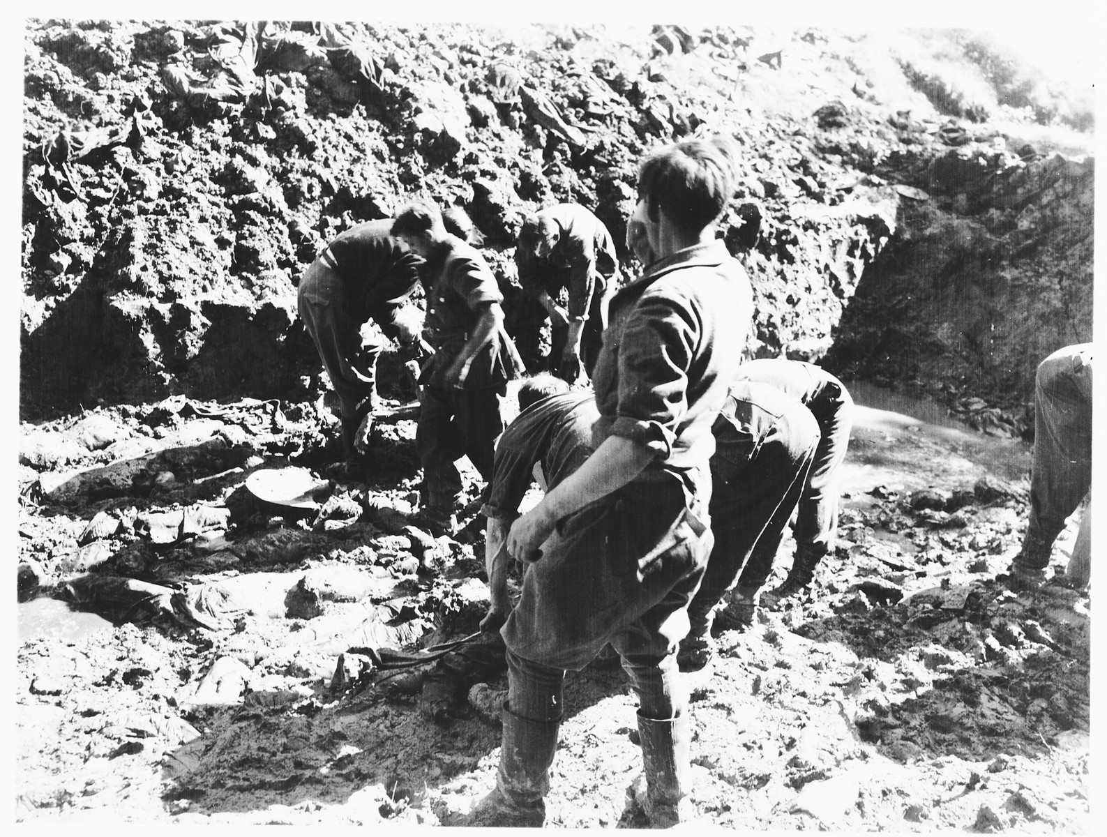 German prisoners of war from a nearby internment camp are forced to exhume bodies from a mass grave found near the town of Nammering.
