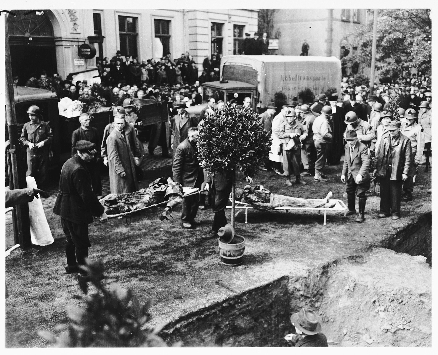 Under the direction of American soldiers, German civilians bury the bodies of 71 political prisoners, exhumed from a mass grave near Solingen-Ohligs, in new graves in front of the city hall.    The victims, most of whom were taken from Luettringhausen prison, were shot and buried by the Gestapo following orders to eliminate all Reich enemies just before the end of the war.