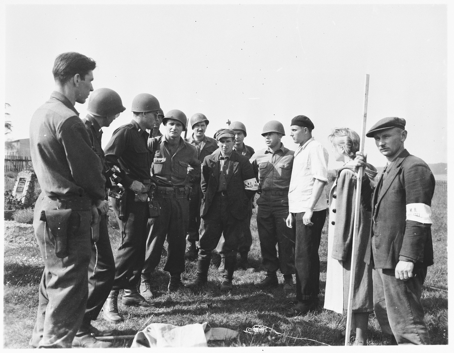 American military authorities question a German civilian from Estedt (pictured third from right) about the atrocity that occurred near the town.