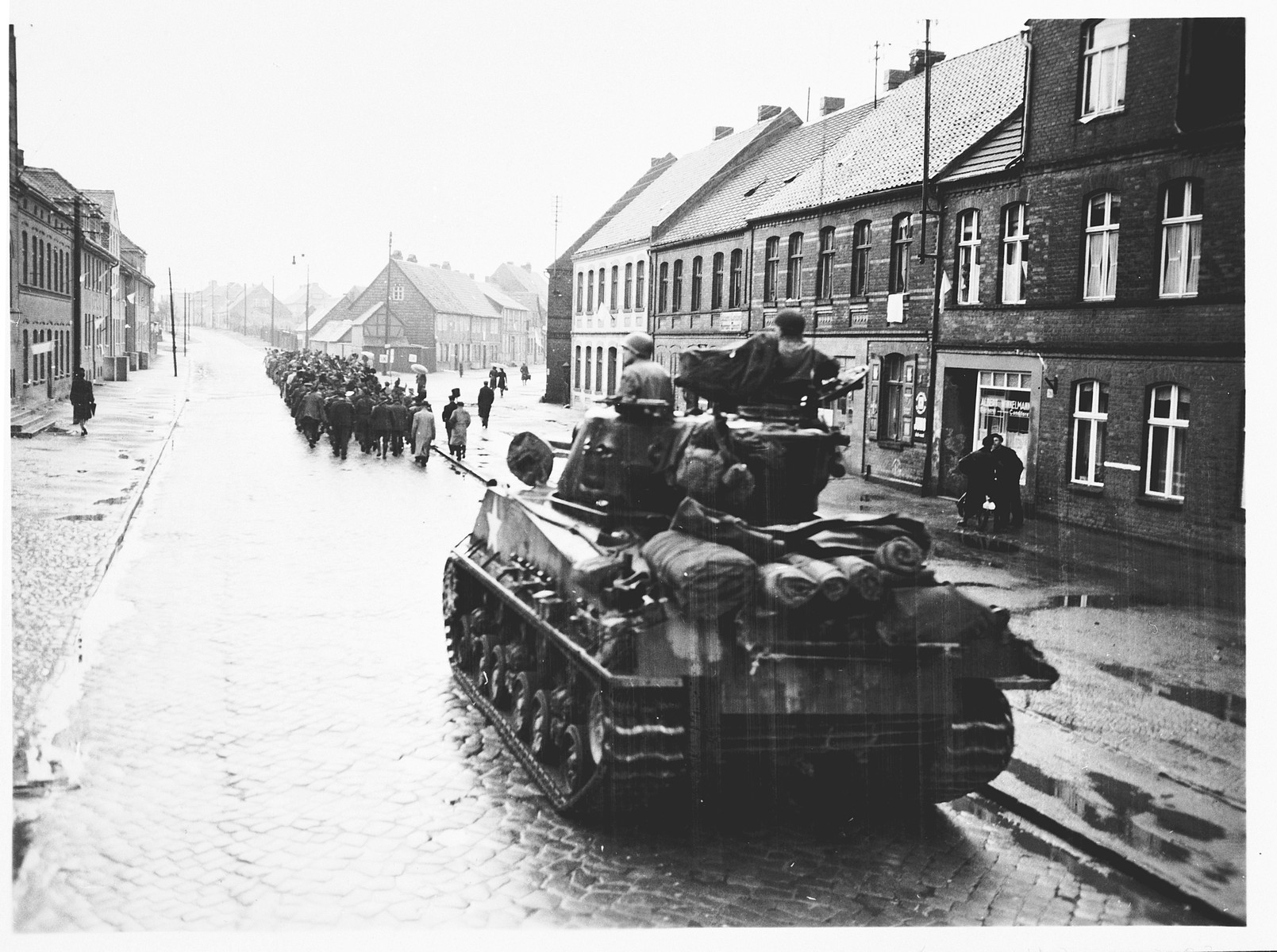 An American tank follows German civilians from Gardelegen who are marching to a barn just outside the town, where they will dig graves for over 1,000 prisoners killed by the SS inside the barn.