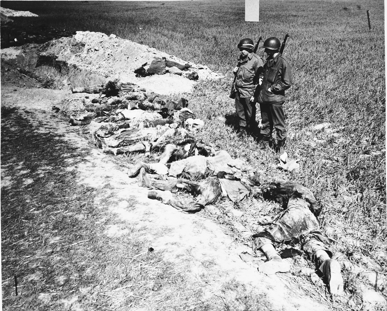 American soldiers look at the exhumed bodies of prisoners who were burned alive in a barn outside of Gardelegen.  In the background lies the mass grave.