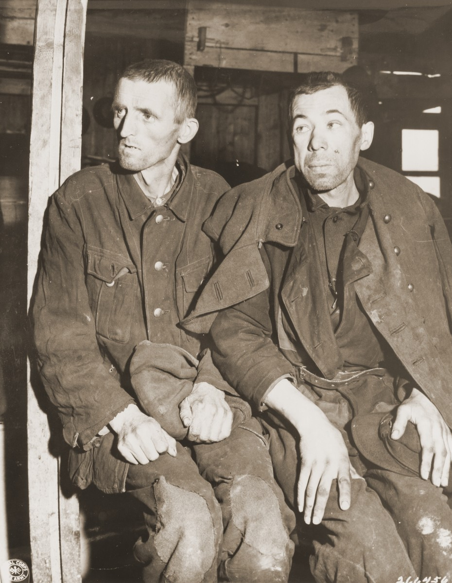 "Two emaciated Soviet POWs sit on a bunk inside a barracks in the newly liberated Hemer POW camp.  Original caption: ""Two former Soviet POWs display the effects of camp imprisonment through their appearence. The man on the left is so thin and weak from starvation that he can hardly stand up by himself. The other's swollen face also indicates suffering from starvation. When the 75th Infantry Division of the U.S. Ninth Army liberated the camp at Hemer, about 22,000 prisoners were liberated. Approximately 9,000 prisoners were hospitalized for tuberculosis, dysentery, malnutrition and typhus fever."""