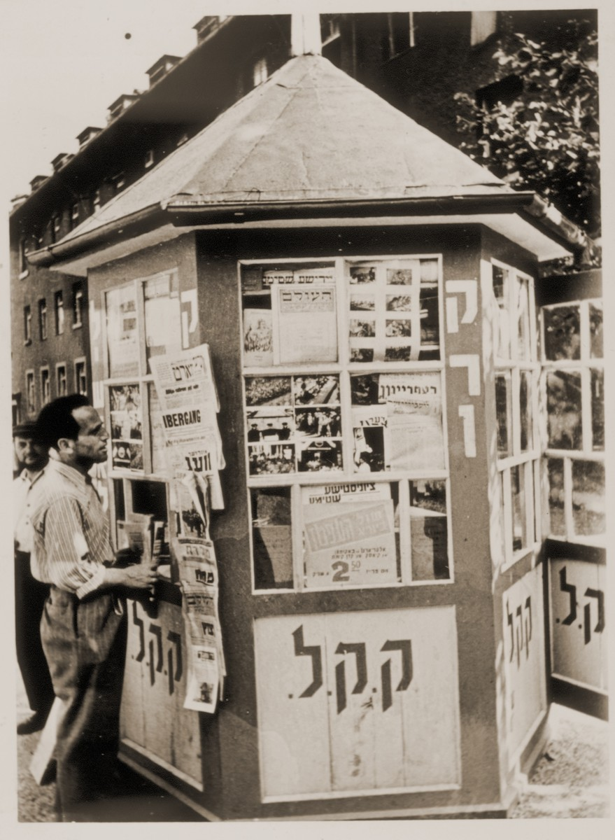 A Jewish DP reads the announcements posted on the newspaper kiosk at the Neu Freimann displaced persons camp.  The kiosk is sponsored by the Keren Kayemet L'Israel [Jewish National Fund].