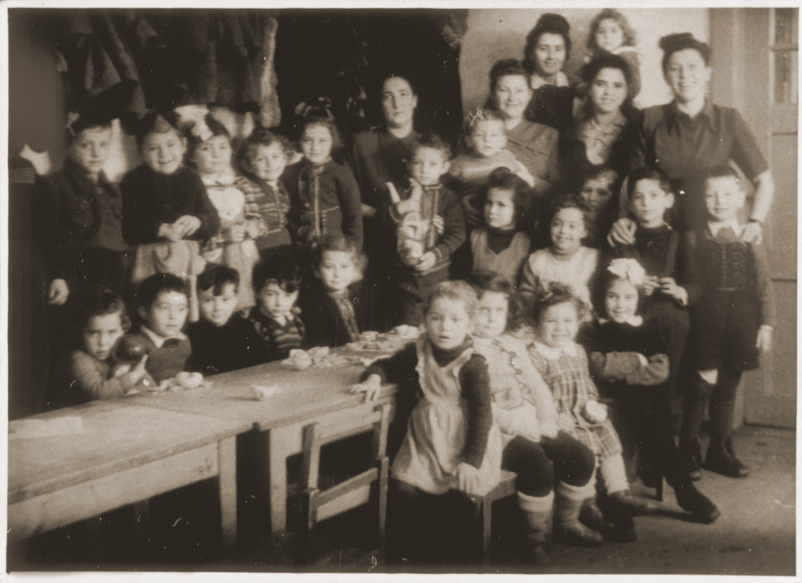 Jewish kindergarteners and five teachers and aides in a classroom at the Landsberg DP camp.    Dorit Mandelbaum stands in the second row, third from the right.