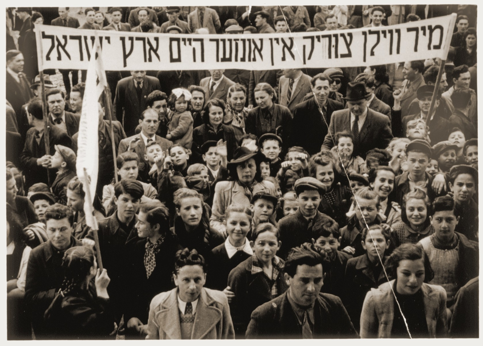 """A large crowd of Jewish DPs participate in a demonstration protesting British immigration policy to Israel at the Neu Freimann displaced persons camp.  They stand beneath a Yiddish banner which proclaims, """"We want to go back to our home in the Land of Israel."""""""