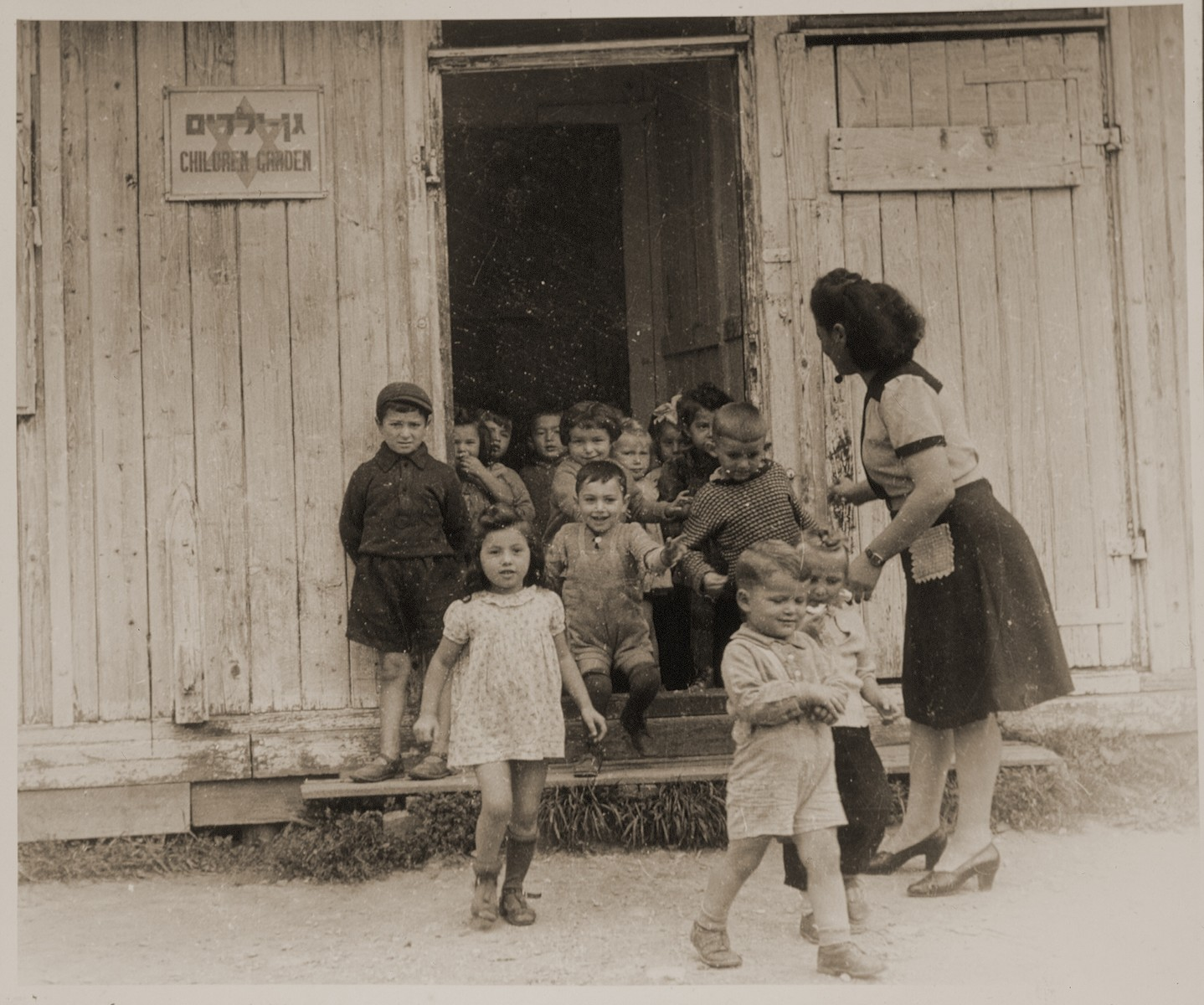 "A teacher ushers children through a doorway of a kindergarten in a DP camp in Sankt Marien.  Family album bearing the title ""Motoring/Jewish DP camp/St. Marein [Sankt Marien]/School,"" that belonged to Moritz Friedler.  In 1946 and 1947, he served as a social worker with the Jewish Committee for Relief Abroad at the Sankt Marien DP camp in the British zone of Austria. Friedler subsequently became the JDC's Area Director in Linz, Austria.  The photo album documents Jewish DP life in both places."
