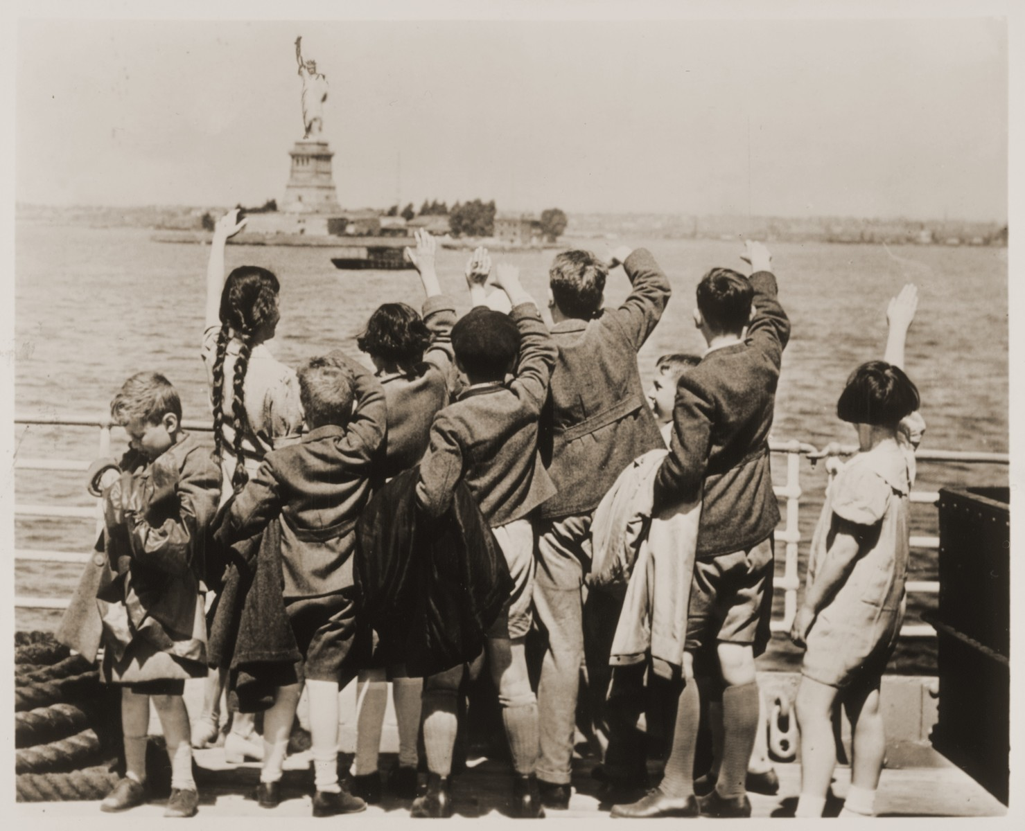 Jewish refugee children wave at the Statue of Liberty as the President Harding steams into New York harbor.  These children are among a group of fifty Jewish refugees (25 boys and 25 girls) from Vienna, aged 5 to 14, who are en route to Philadelphia, where they will be placed with foster families.  The children were accompanied by Gilbert J. Kraus, a Philadelphia attorney, and his wife Eleanor, who had worked for months to secure their admission into the U.S.  Among those pictured is Johanna Braun Gitlin (two, long braids).